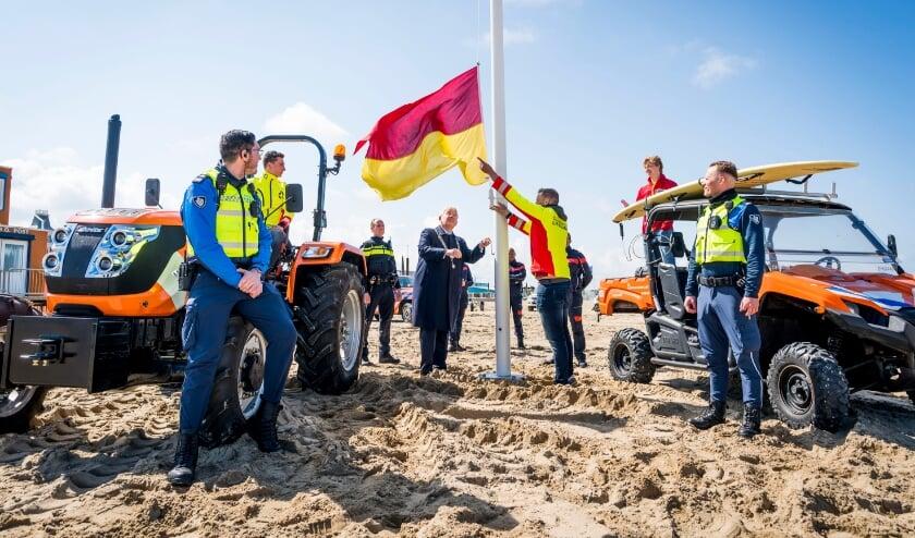 <p>Samen met lifeguards van de Haagse Vrijwillige Reddingsbrigade (HVRB) en Veiligheidsregio Haaglanden (VRH) hijst burgemeester Jan van Zanen voor het eerst de geel/rode vlag dit seizoen. Foto: Valerie Kuypers</p>