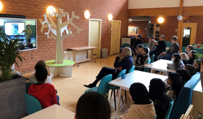 <p>Samen met de leerlingen van groep 8 van OBS Ypenburg bekijkt commissaris van de Koning Jaap Smit (m.) het winnende filmpje. Foto: Astrid Abbing</p>