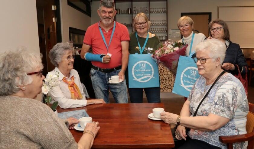 <p>Vrijwilligers van de catering en Ellen Tolhuisen (met bloemen) van Bewonersorganisatie Leidschenveen BOL met drie dames die gezellig koffiedrinken op de dag van de opening. Foto: Jan van Es</p>