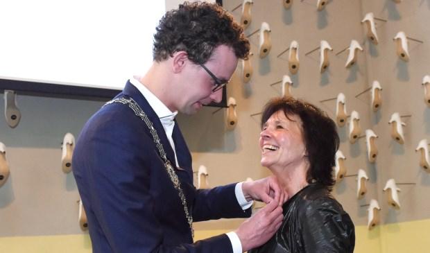 Locoburgemeester Martijn van der Putten speldt de onderscheiding bij Marieke Sieraad op. Foto: Hoedemaekers.