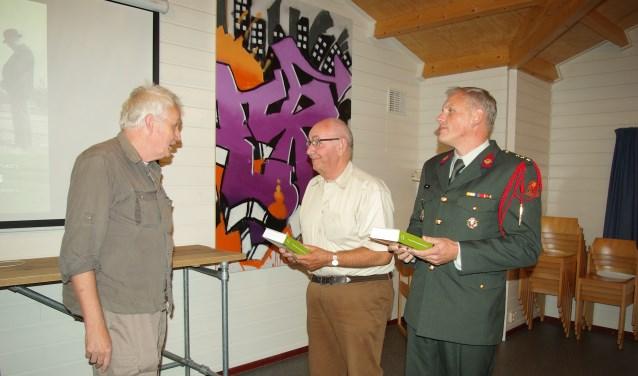 Hans Sakkers overhandigt de eerste twee boeken.