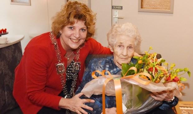 Carla Brugman zet de 100-jarige mevrouw Veldpaus-Thijssen in de bloemetjes.