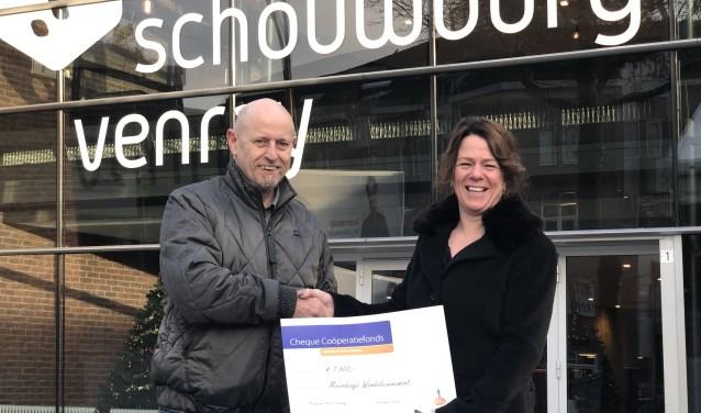 Voorzitter André Tonen ontvangt de cheque uit handen van  Chantal Scherders-Thijssen van het Coöperatiefonds Rabobank.