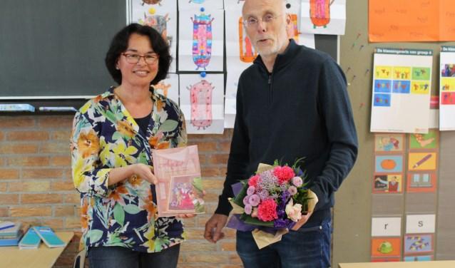 Elly Doornbosch overhandigt het boek aan directeur Cor Both en hij geeft bloemen aan Elly.
