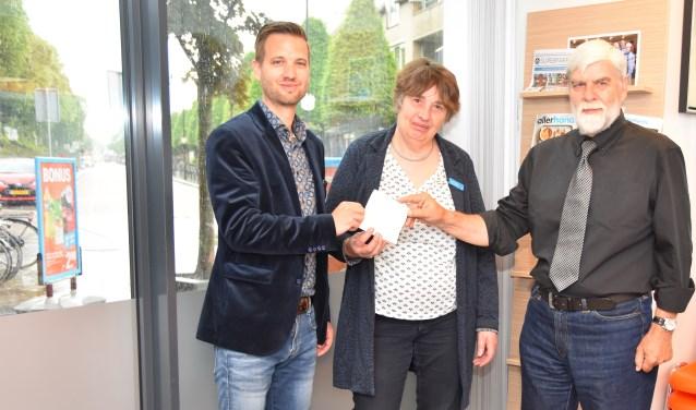 Wim Eijbers, voorzitter van de afdeling Alzheimer Nederland overhandigt de stickers aan de beide filiaalhouers, Meik de Raadt en Jasper Pieterse.