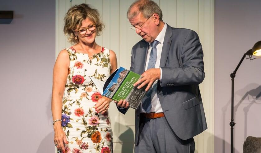 Vertrekkend directeur-bestuurder Simon van Nieuwaal overhandigd het 'Een eeuw goed wonen' aan burgemeester Grootenboer.