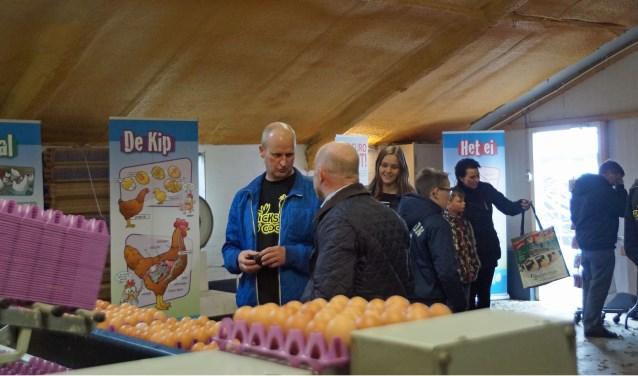 Op de voorgrond staat Bart van Stiphout (blauwe jas) die een bezoeker een en ander toelicht in de eiersorteerruimte  | Fotonummer: a97f1d