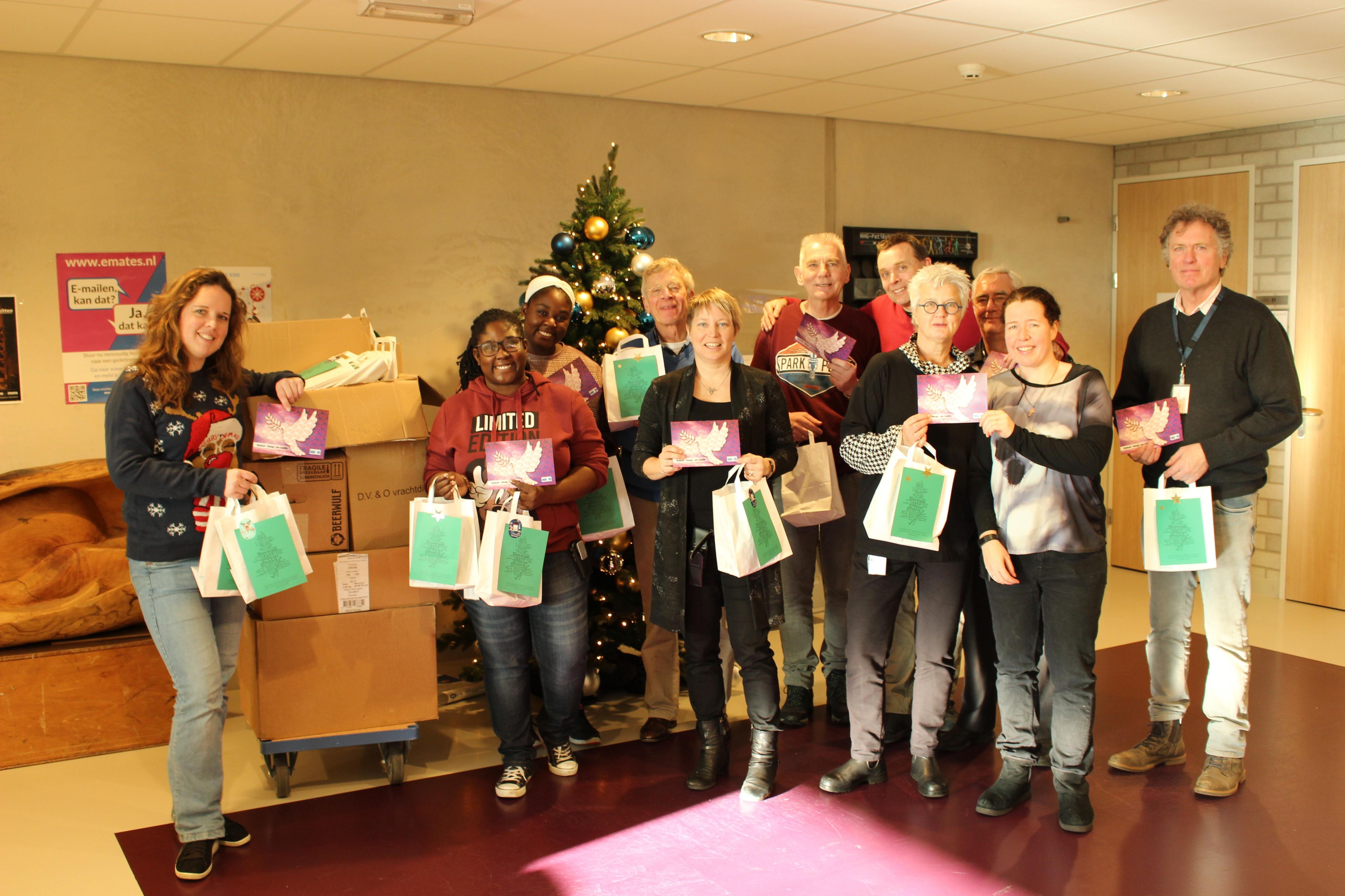 Vrijwilligers DSG De Sluis en medewerkers Geestelijke Verzorging JCZ Zaanstad delen attenties uit. Links de kar met de 850 pakketjes.