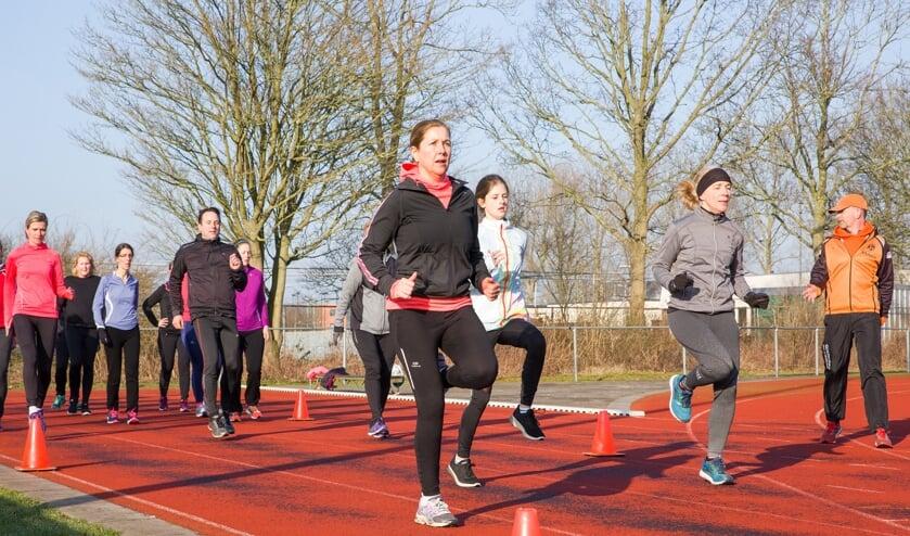 Hera-trainer Henk van Dijk (r) helpt deelnemers aan de CityRun zich op de juiste manier voor te bereiden: 'In groepsverband trainen verhoogt het plezier.'