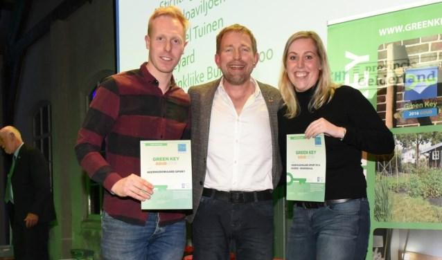Danny de Boer en Jill Zuurbier van het Green Team Heerhugowaard Sport NV, met tv-presentator Harm Edens in hun midden.