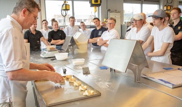 De leerlingen kijken nieuwsgierig toe hoe meesterbakker François Brandt (l) de Scandinavische broodjes ovenklaar maakt.