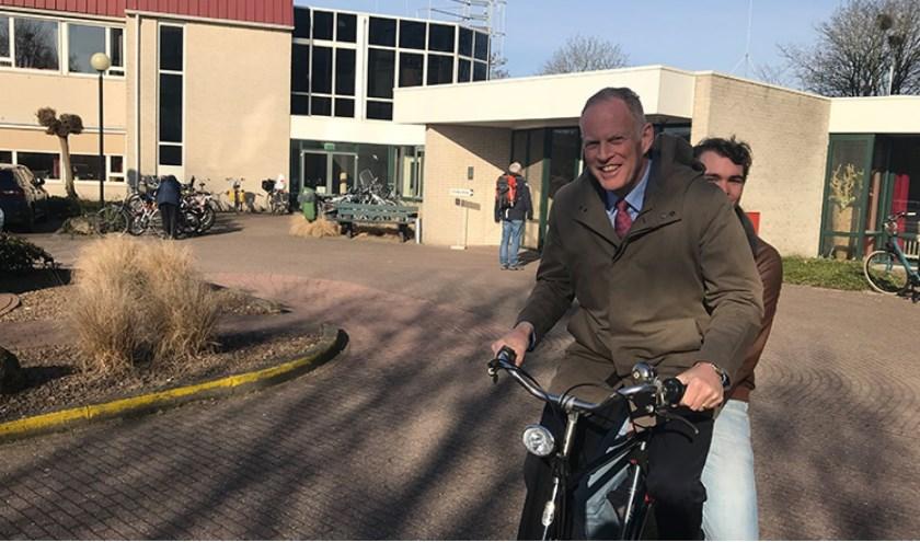 Han ter Heegde, de voormalige burgemeester van Heerhugowaard, brengt kiezers op de fiets naar het stembureau.