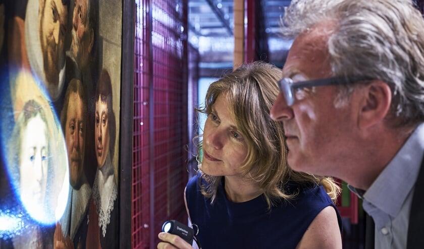 Conservator Christi Klinkert toont beschadigingen aan directeur Patrick van Mil.