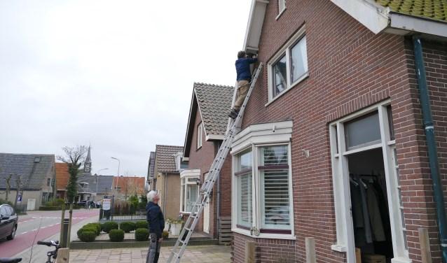 Arjan van Poecke hangt huiszwaluwnest op aan huis in de Kerkbuurt.