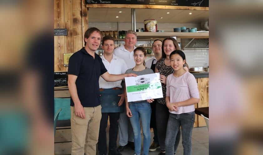 Het personeel van de BioExpress reikt de prijs uit aan Team Sushi-burger.