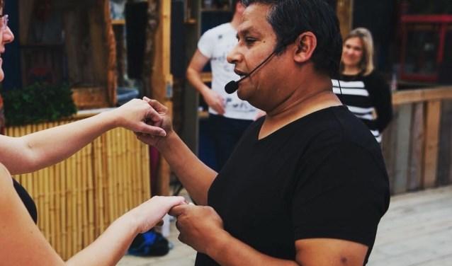 Docent leert deelnemer de passen van de Salsa.