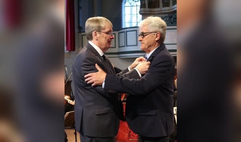 Het lintje wordt opgespeld door de burgemeester.