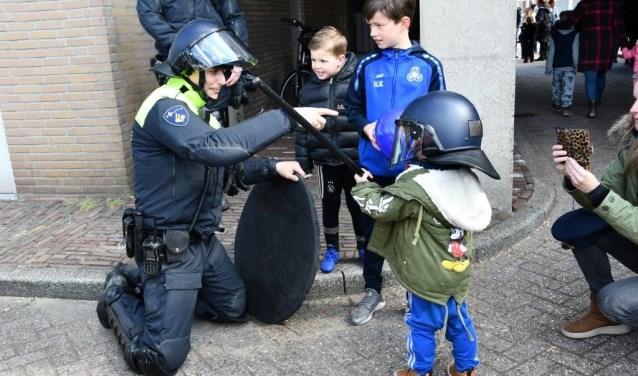 Deze politieman legt de jongste jeugd iets uit.
