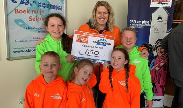 De teams overhandigen Marlies Driessen een cheque van 850 euro voor KiKa.