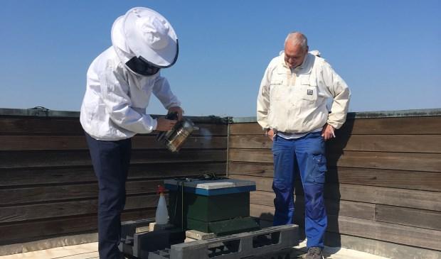 Links in het imkerpak wethouder Simon Broersma en rechts imker Jan Koomen. Simon Broersma houdt met de beroker het bijenvolk rustig.