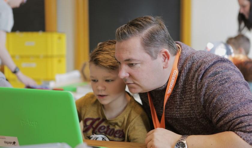 Kinderen leren programmeren onder leiding van vrijwilligers in de Coderdojo.
