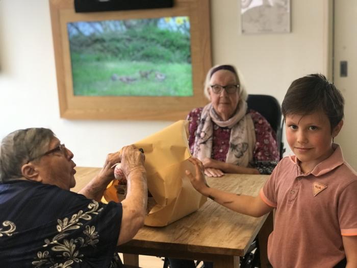 Abel uit groep 5 geeft een van de Paasmanden aan bewoners van Oudtburgh