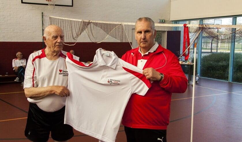 Ton Reuser (88) krijgt het eerste sportshirts uit handen van Ton Schomakers (r) voorzitter Hartenjagers Sport Zaanstreek.