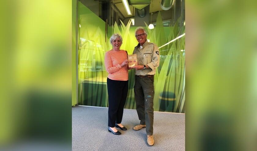 Auteur Cockie Vlietman overhandigt het eerste boek aan een boswachter.