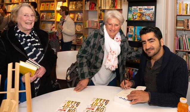 De auteur gaat graag in op het verzoek van Wienny Reuser (midden) om iets in het boek te schrijven. Links Annemiek Scheepers, de vriendin van Wienny.