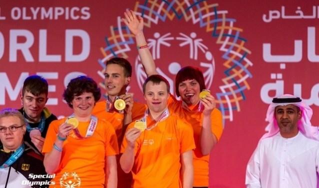 René, tussen zijn teammaatjes, laat zijn gouden medaille zien.