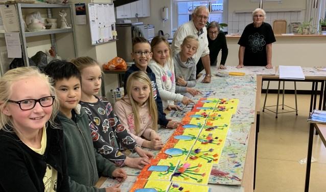 De kinderclub van de KsK'80 met hun eigen voorjaarskunstwerkjes. Met op de achtergrond drie enthousiaste docenten.