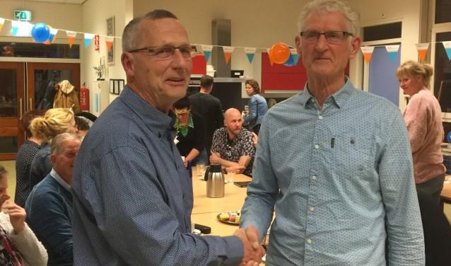 Oud-politieman Frans van Diepen (rechts), wordt bedankt door Arie Ham van de Commissie Verkeersbrigade Waarland.