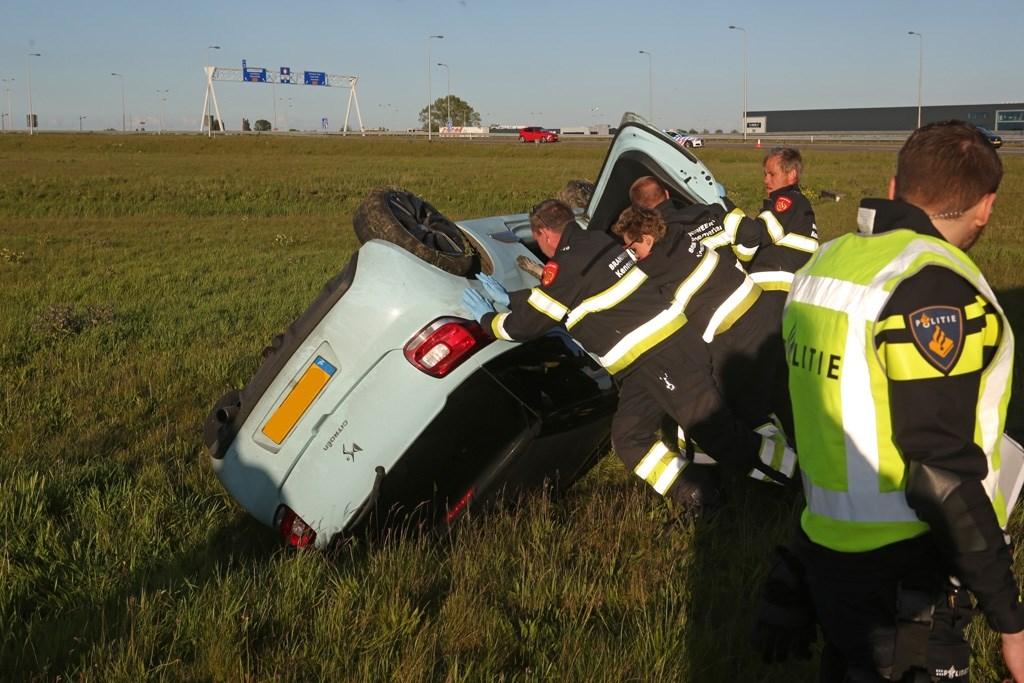 Brandweerlieden helpen de auto weer op zijn wielen.  (Foto: Rowin van Diest) © rodi