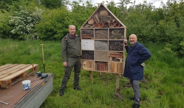 Boswachter Paul Bot (l) en onderwijsassistent Babis Saridakis begeleiden de scholieren bij het maken van de bijenhotels.
