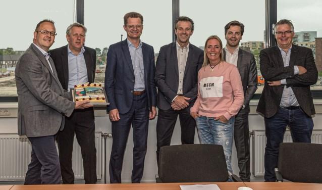 Vertegenwoordigers van beide bedrijven gingen maar wat graag op de foto. Uiteraard met taart.