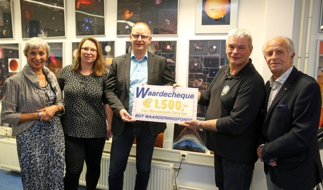 Voorzitter Paul Volman (tweede van rechts) neemt namens Sterrenwacht Saturnus de cheque in ontvangst uit handen van het bestuur van het Bot Waarderingsfonds.