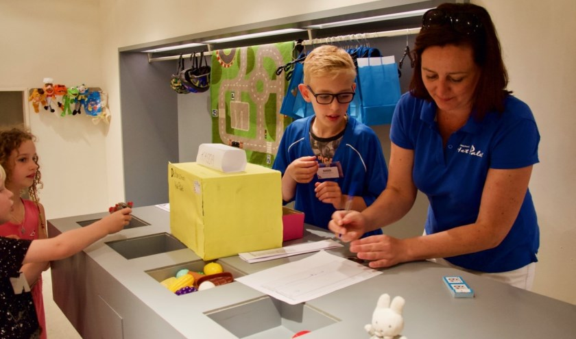 Een leerling en een begeleider helpen een klant.