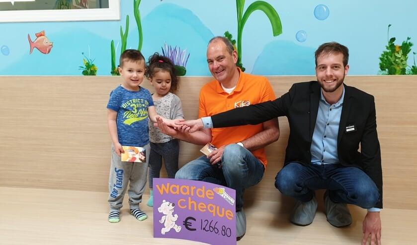 René Oud van KiKa krijgt de cheque uit handen van kindjes van 't Schelpje, Rechts Denny Laan van sponsor 'Jumbo Monique'.