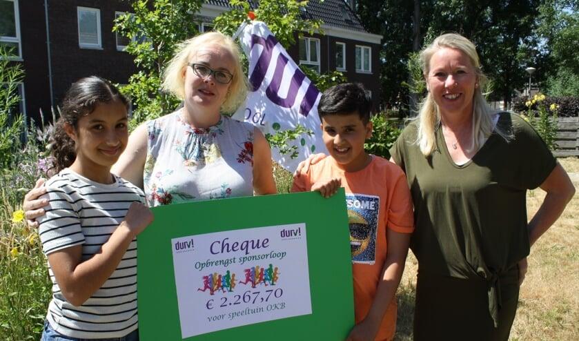 DURV! leerlingen Aya en Sani overhandigen de cheque aan Cretienne Hoekman van speeltuin OKB.