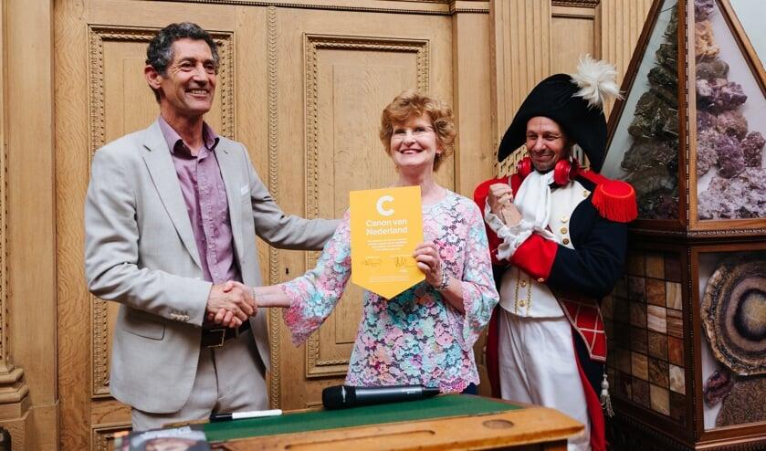 Teus Eenkhoorn, directeur Nederlands Openluchtmuseum en directeur van Teylers Museum Marjan Scharloo met het convenantbord. Napoleon kijkt toe.