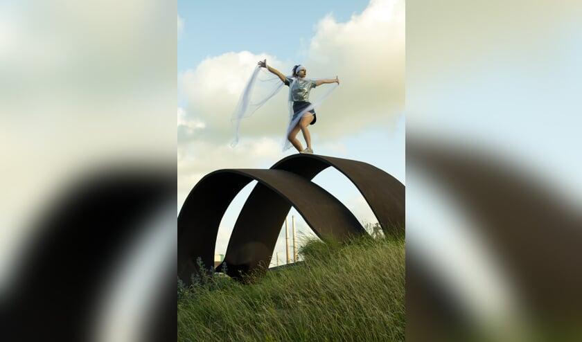 Dansend kunstenaar Sophia Maria Kienhuis op het beeld van Nico Betjes.