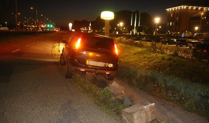 Hoe de vrouw op de betonblokken terechtkwam, is niet duidelijk, maar haar auto moest er af getakeld worden.
