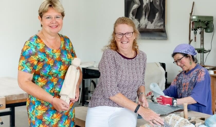 Hanna Tjerks (l) en Marion Bakker van Atelier 6. Op de achtergrond is een kunstenares aan het werk.