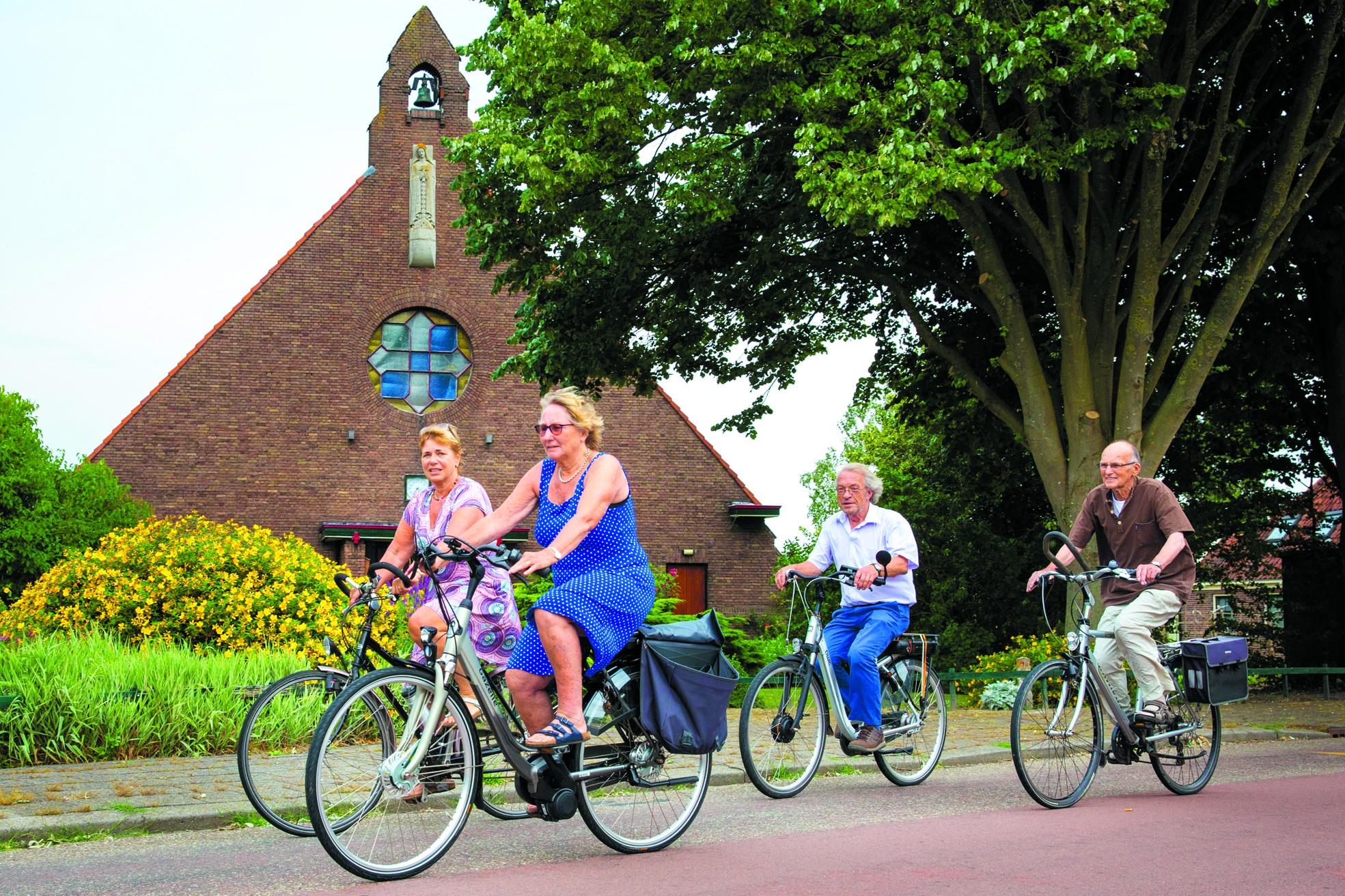 Loes Siedenburg, Lies van der Spek, Gerard van der Vliet en Jaap Visser (v.l.n.r.) van Drechterland Mondiaal fietsen langs de Theresiakapel in Hem, een van de deelnemende kerkjes. (archieffoto Vincent de Vries/RM)