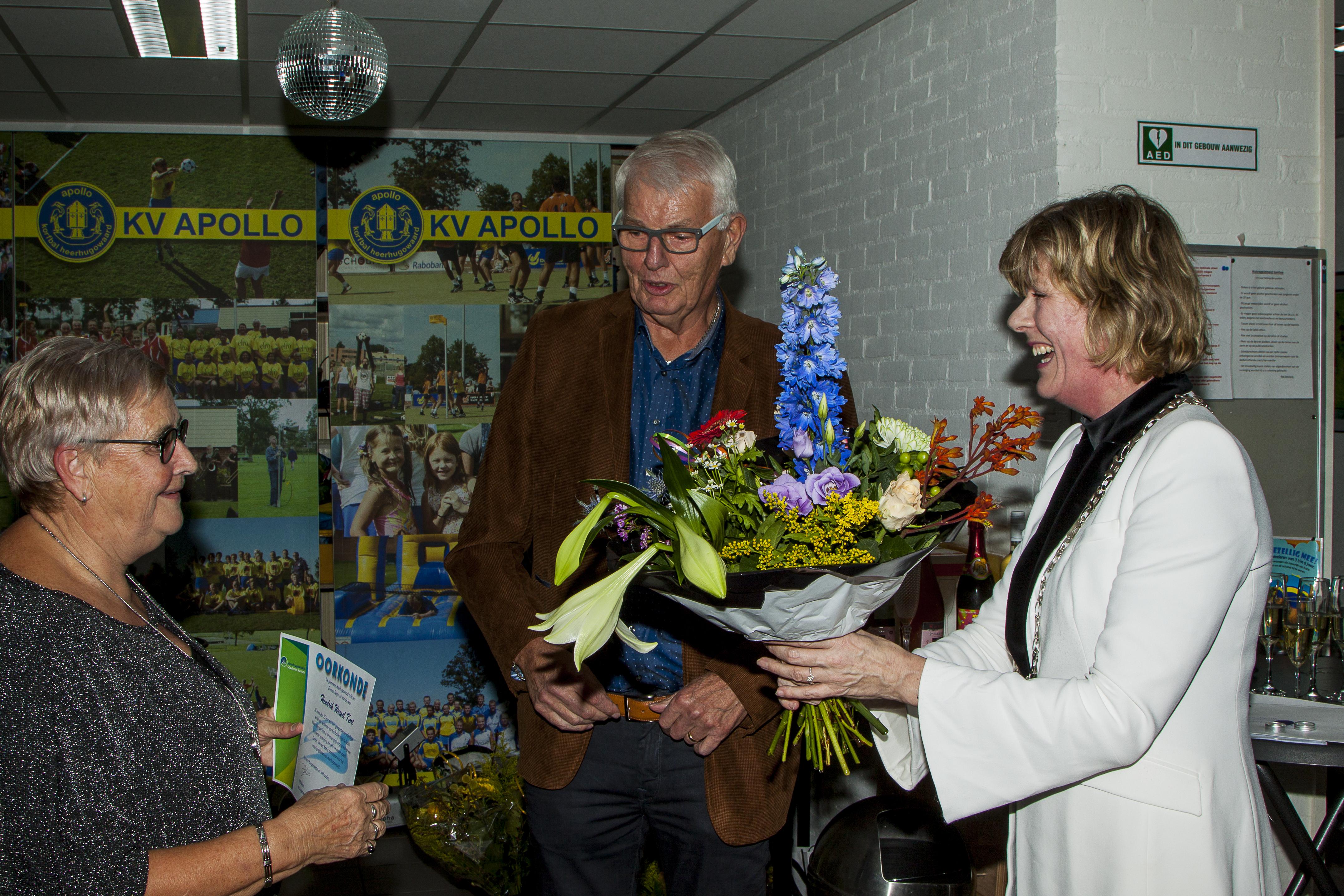 Henk Kort en zijn vrouw (l) werden door wethouder Monique Stam in het zonnetje gezet. (aangeleverde foto)