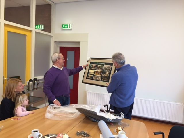 Een schilderij met prenten uit de privécollectie van Nico Boerma wordt overhandigd aan Henk van Breemen. (Foto: aangeleverd)