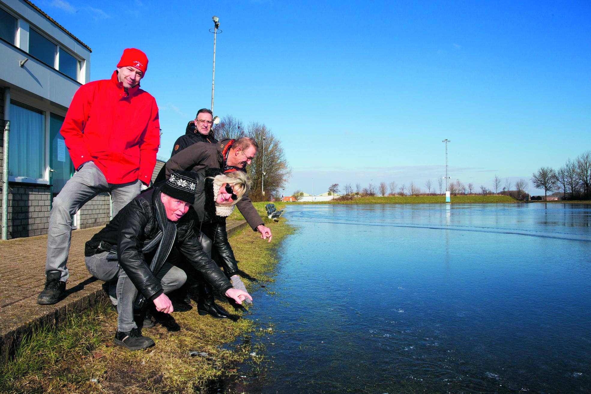 Arjan Mak (l) checkte afgelopen maandag - samen met een aantal nieuwsgierigen - het ijs van de ijsbaan in Hoogkarspel. (Foto: Vincent de Vries/RM)