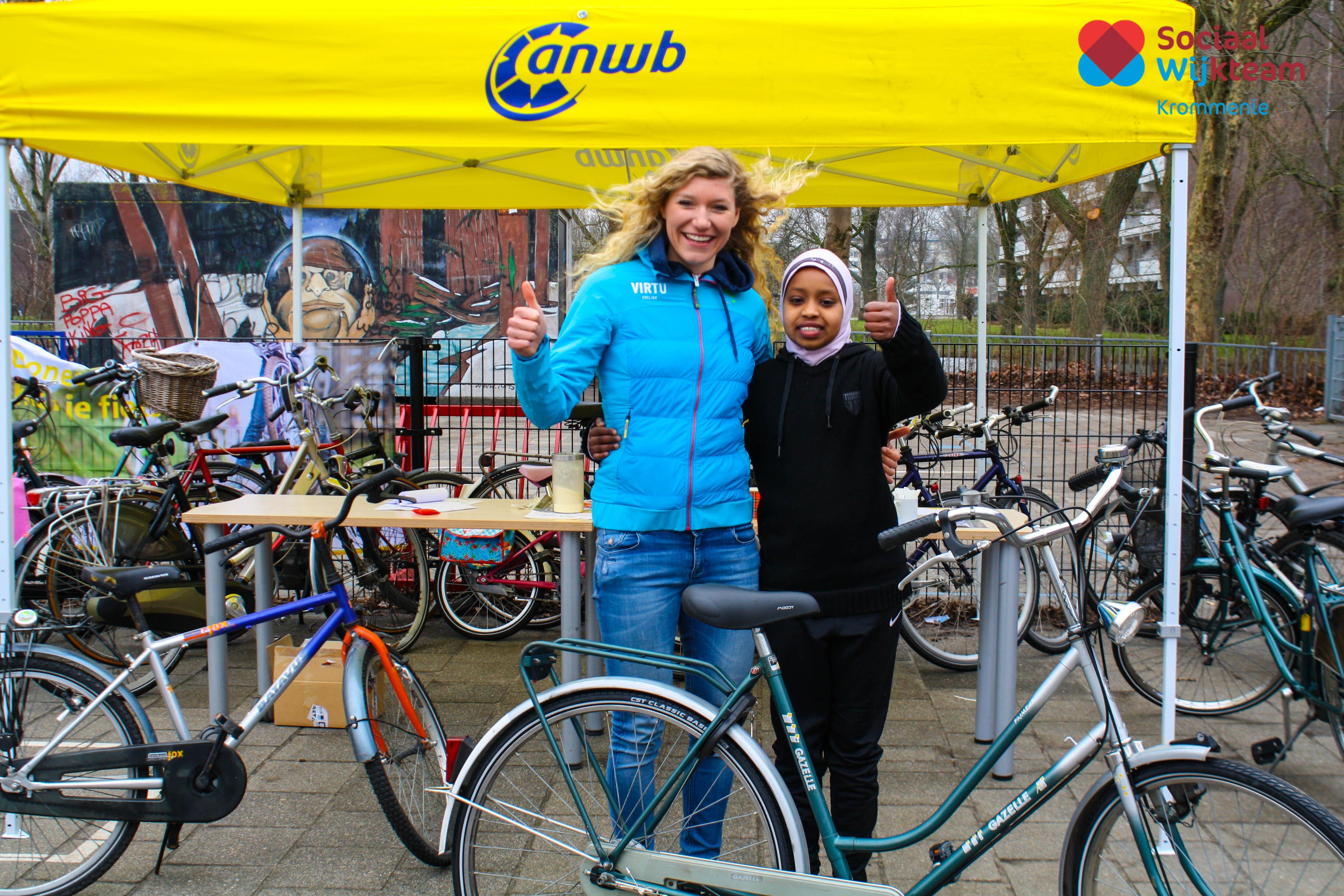 Professioneel wielrenster Claudia Koster met één van de kinderen die een fiets ontvangt vanuit het Kinderfietsenplan van de ANWB. (Foto: swtzaanstad)