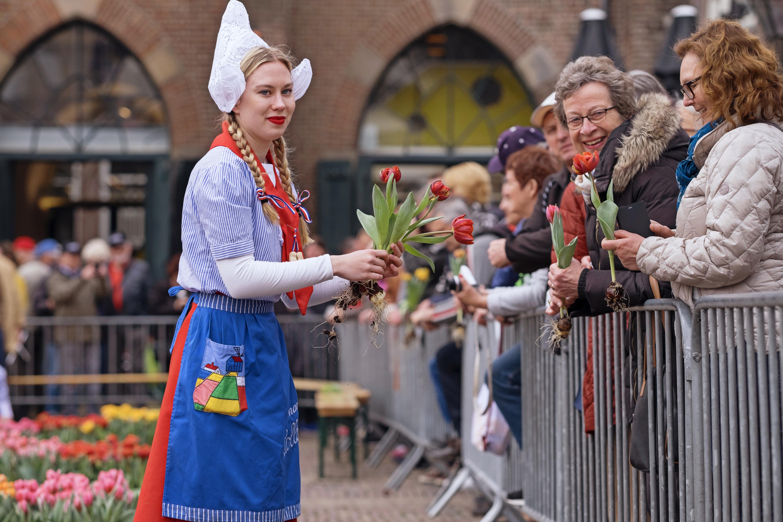 Kaasmeisjes delen tulpen uit aan bezoekers kaasmarkt. (Foto: aangeleverd)