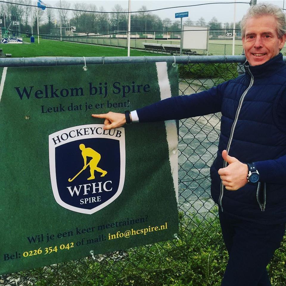 Voorzitter Gerard Welling voor de nieuwe banner bij de ingang van hockeyvereniging Spire. (Foto: aangeleverd)